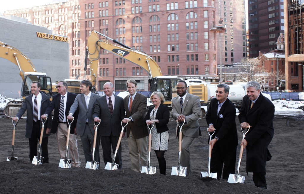 Members of the SkyHouse Denver development team and the City of Denver stand poised to break ground.